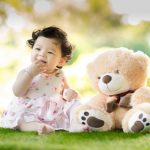 Image of Baby Sitting on Green Grass Beside Bear Plush Toy at Daytime