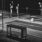 Image of Grayscale Photography of Waiting Shed Near Open Road at Night