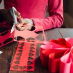 Image of a Girl cutting red paper for Valentines